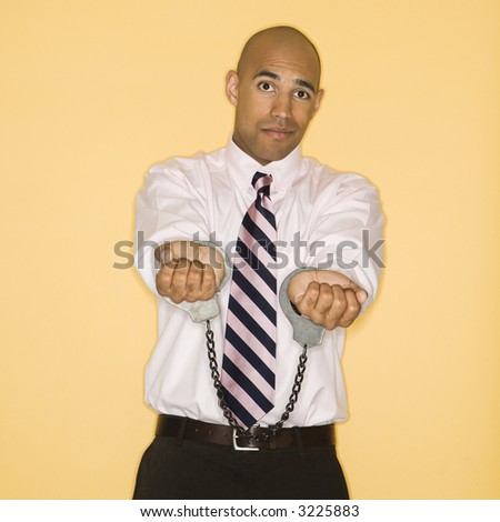 African American man wearing handcuffs and looking sad. - stock photo