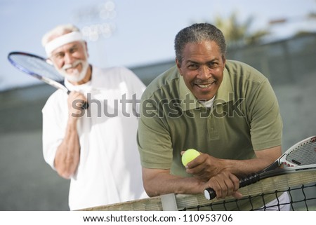 African American man with a friend playing tennis - stock photo