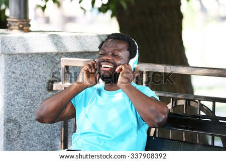 African American man with headphones on bench in park