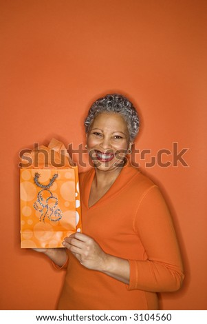 African American mature adult female holding gift bag smiling.