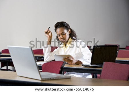 African American medical student in lab coat studying in classroom - stock photo