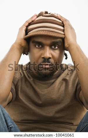African-American mid-adult man holding head wearing hat looking at viewer.