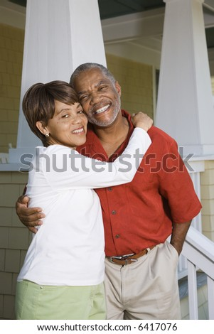 African American middle aged couple hugging and smiling at viewer. - stock photo