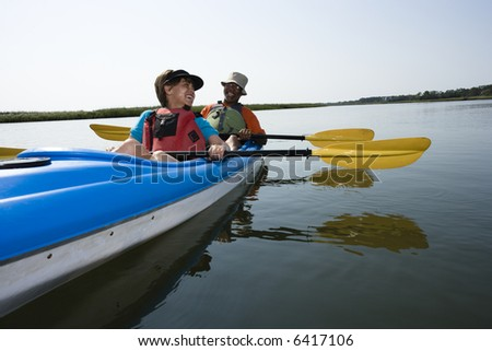 African American middle-aged couple sitting in kayak on lake smiling and laughing. - stock photo
