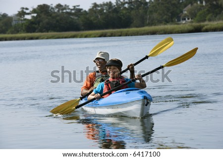 African American middle-aged couple smiling and paddling kayak. - stock photo