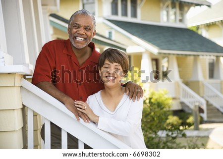 African American middle aged couple standing together on stairs outside home. - stock photo