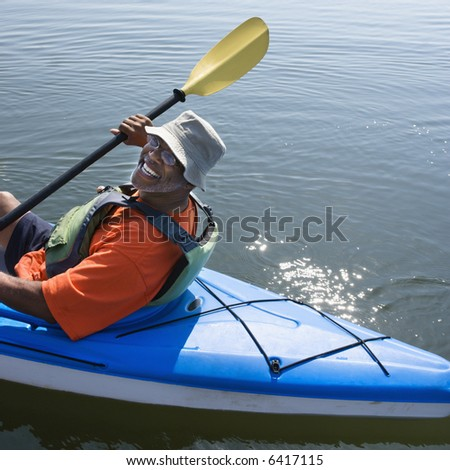 African American middle-aged man smiling at viewer in kayak.