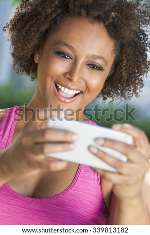 African American mixed race young woman or girl taking selfie photograph using smartphone or cell phone - stock photo