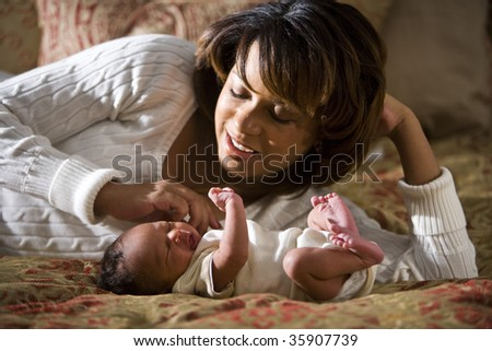 African American mother admiring her newborn child - stock photo