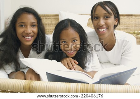 African American mother and daughters on bed with book - stock photo