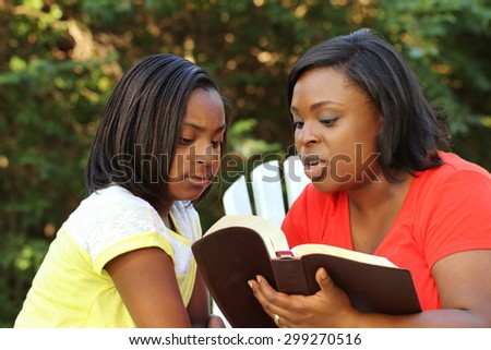 African American Mother Reading to her Daughter - stock photo