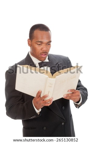 African American preacher reading from a bible, isolated over white - stock photo