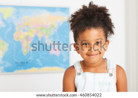 African american preschool girl in classroom with world map