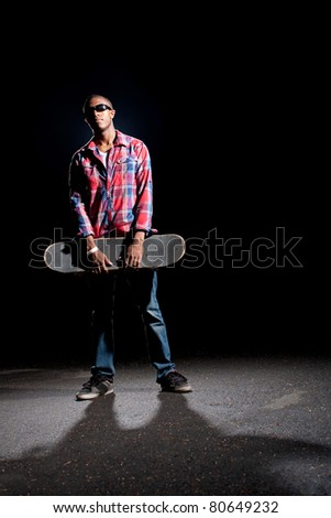 African American skateboarder wearing sunglasses holding his skateboard under dramatic lighting with dramatic shadows. - stock photo