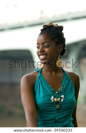african american smiles while sitting by bridge - stock photo
