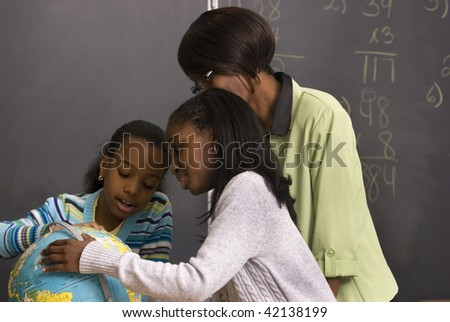 African American students and teacher search for different countries on the globe; enjoying a classroom activity - stock photo