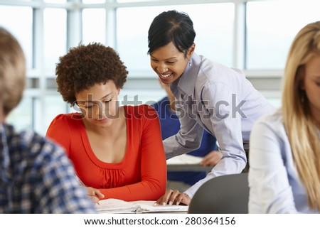 African American teacher helping student in class - stock photo
