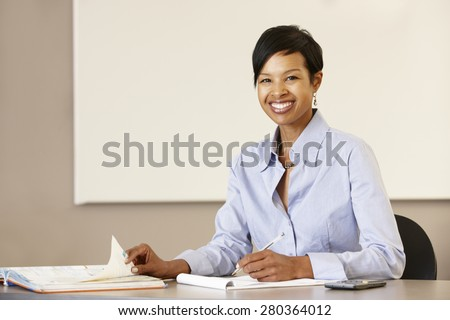 African American teacher working at desk - stock photo