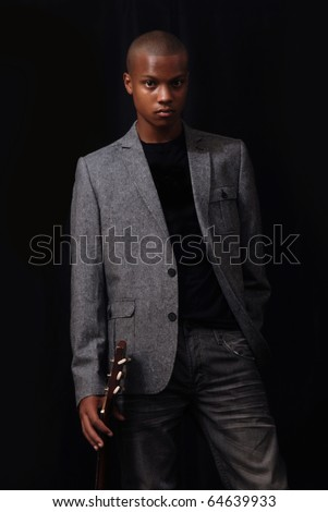 african american teen idol stands with guitar - stock photo