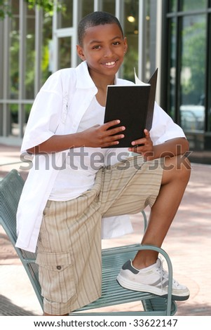 African American teenager boy reading a book on a bench outdoors, city street - stock photo