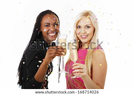 African american woman and white woman toast with sparkling wine - stock photo