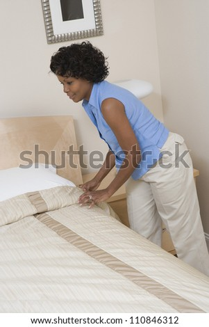 African American woman arranging bed at home - stock photo