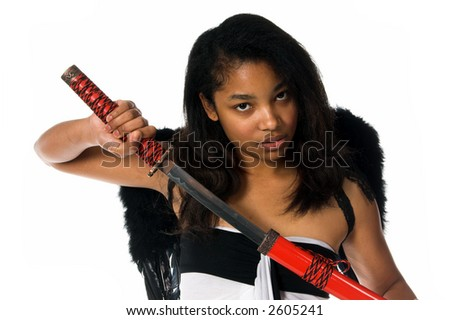 African American woman as a Ninja Angel with black feather wings and an intense expression draws her ninja sword from it's sheath - stock photo