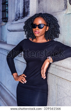 African American Woman casual street fashion. Wearing long sleeve dress, sunglasses, wristwatch, a black girl standing against wall, hand resting on hips, relaxing. Filtered look with purple tint. - stock photo