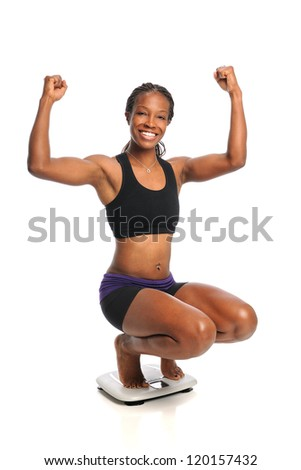 African American woman celebrating weight loss standing on scale - stock photo
