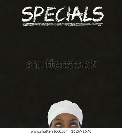 African American woman chef thinking with chalk specials sign on blackboard Background - stock photo