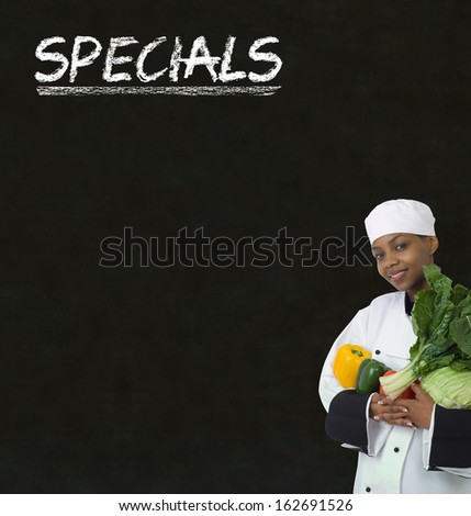 African American woman chef with chalk specials sign on blackboard background - stock photo