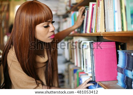 African American woman choosing a book in library.