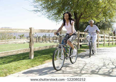 African American woman cycling with her mother in park by wooden fence - stock photo