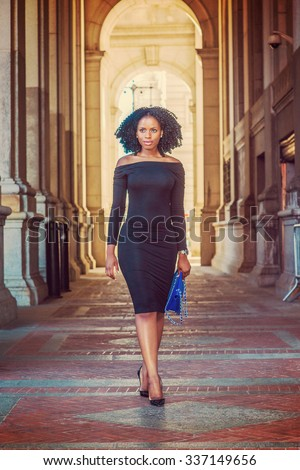 African American Woman Fashion in New York. Wearing long sleeve, slim, off shoulder dress, carrying blue bag, young lady walking on vintage style, narrow street, going to work. Instagram effect.  - stock photo