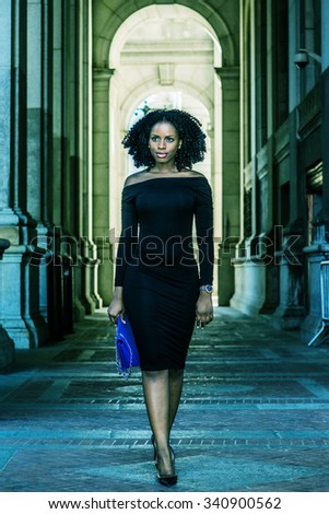 African American Woman Fashion in New York. Wearing long sleeve, slim, off shoulder dress, carrying blue bag, a young lady walking on narrow street, going to work. Filtered look with green tint.