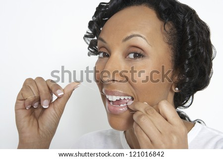 African American woman flossing her teeth