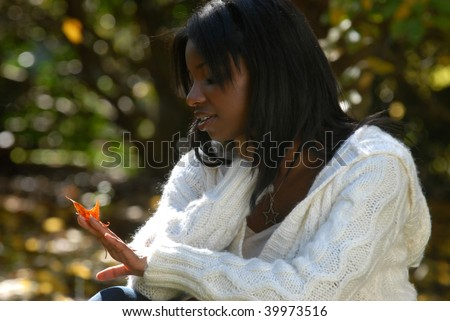 African-American woman gazing at the colors of a fall leaf - stock photo