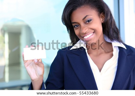 African American woman holding business card at office building - stock photo