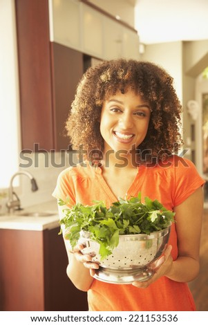 African American woman holding vegetables in colander - stock photo
