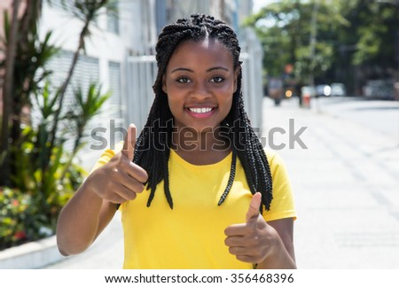 African american woman in a yellow shirt in city showing thumb - stock photo