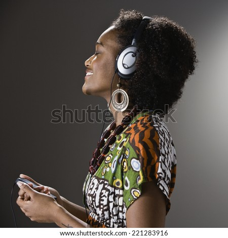 African American woman listening to headphones - stock photo