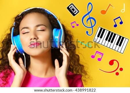 African American woman listening to music in headphones on color background - stock photo