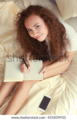African American woman listening to music with earphones on bed - stock photo