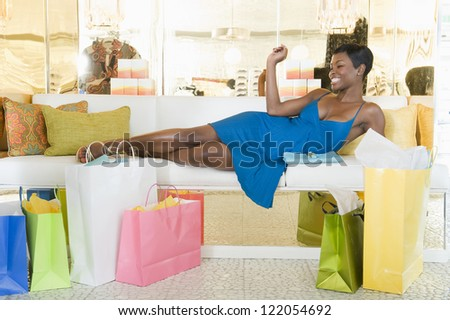 African American woman lying on sofa in a lavish clothing store with shopping bags on floor - stock photo