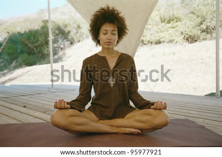 African American woman meditating in screened area - stock photo