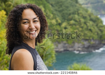 African American woman on cliff over water - stock photo