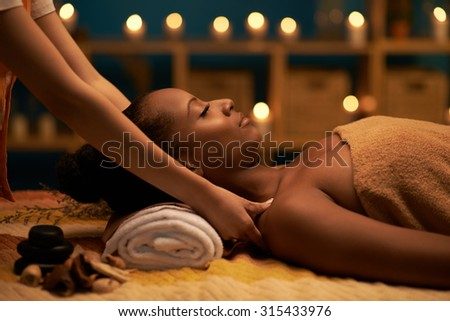 African-American woman receiving relaxing massage in spa salon - stock photo