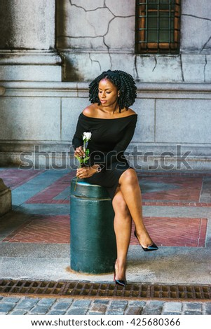 African American Woman seeking love in New York, with braid hairstyle, wearing long sleeve, off shoulder dress, holding white rose, sitting on pillar on street, crossing legs, looking down, thinking. - stock photo