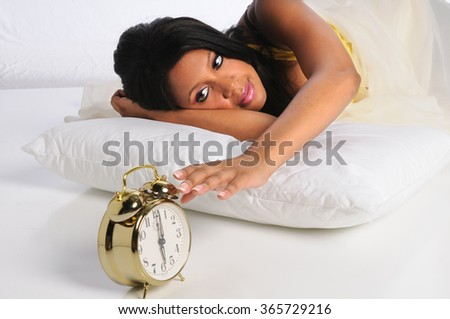 African American woman silencing alarm clock - stock photo