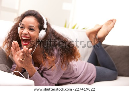 african american woman singing on a sofa wearing white headphones - stock photo